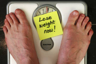 "A man's feet on a scale where a sticky-note reads ""Lose Weight Now"""